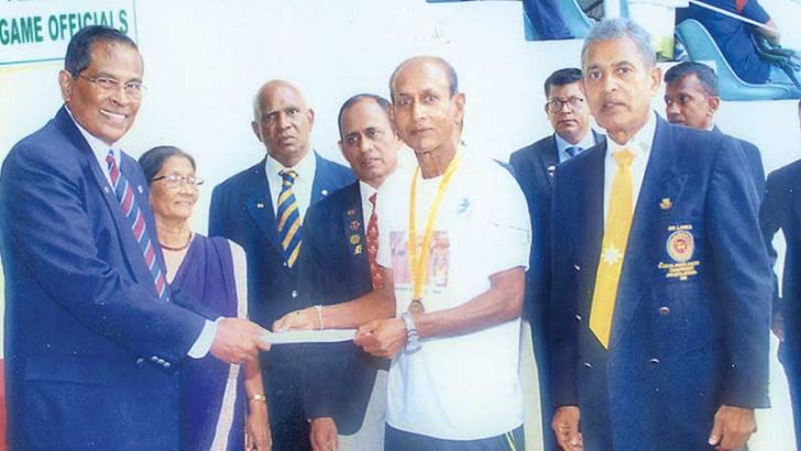 Ranjan Jayathilake receiving his medal and certificate from the Chairman of Masters Athletics Sri Lanka Association P.H. D. Waidyathilake while Secretary of MASL Senani Bogahawatta (right) also in the picture.