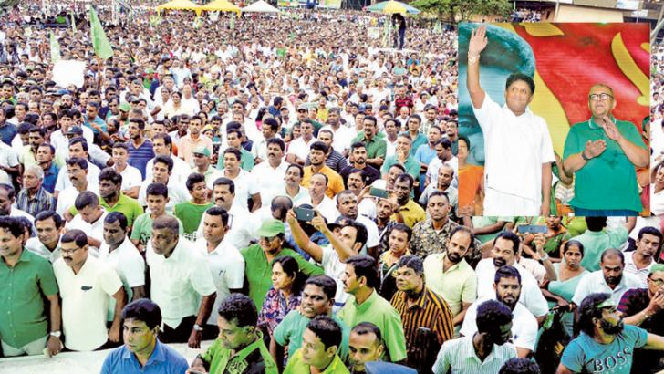 UNP Deputy Leader and Minister Sajith Premadasa and Finance Minister Mangala Samaraweera wave to thousands of supporters who braved the weather to attend the ralley. Pictures by Priyan de Silva