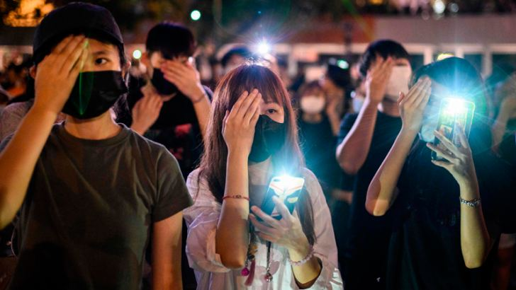 Secondary school students cover their right eye as they hold up their phone torches while attending a rally at Edinburgh Place in Hong Kong Thursday. - AFP