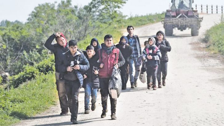 Syrian refugees walk after they crossed the Evros river, the natural boundary with Turkey in northeastern Greece, in the village of Pythio, on April 28, 2018.