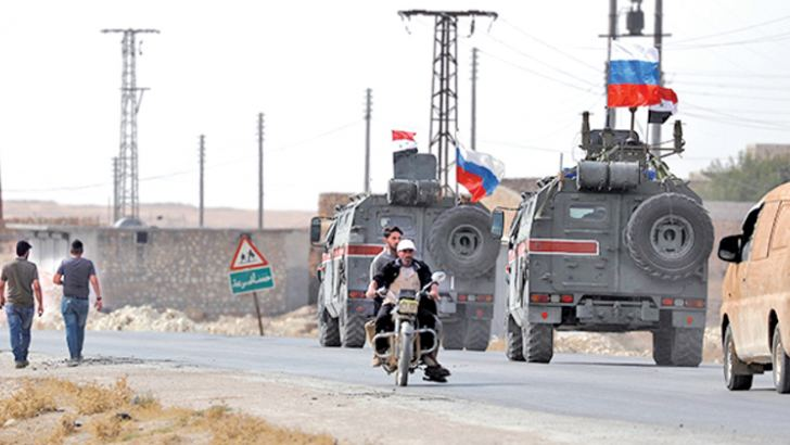 Russian and Syrian national flags flutter on military vehicles near Manbij, Syria.