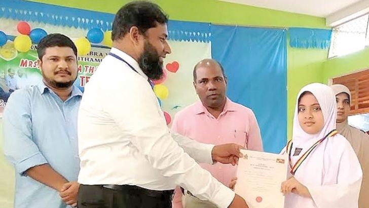 Fathima Jesna receives a prize from Kalmunai Regional Oral Health Medical Officer M.P.Abdul Wajith.