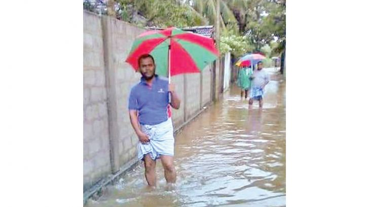 Pedestrians wading through floodwater. Picture by A.B. Abdul Gafoor, Ampara District Group Corr.