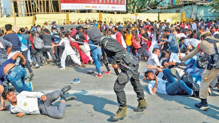 Security personnel use batons to disperse students protesting against the government's Citizenship Amendment Bill (CAB), in Guwahati, India on Wednesday.