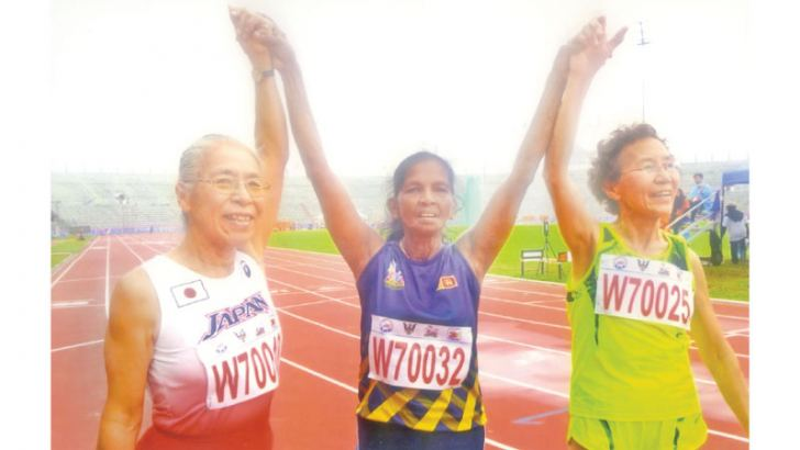 Menike just after winning the 100m gold flanked by Japanese athlete (left-third place) and Chinese athlete (right - second place)