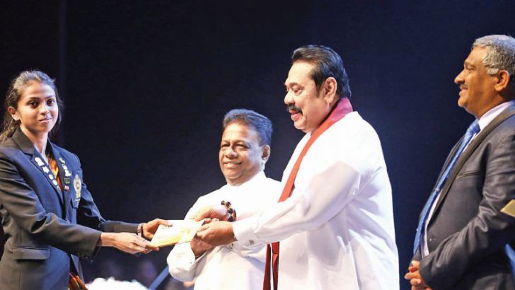 Dilshi Kumarasinghe who won three gold medals in the 400m, 800m and 4x400m relay receiving her cash award from the Prime Minister. Minister of Sports Dullas Alahapperuma and Ministry of Sports secretary K.D.S. Ruwanchandra are also present. Pictures by Sulochana Gamage