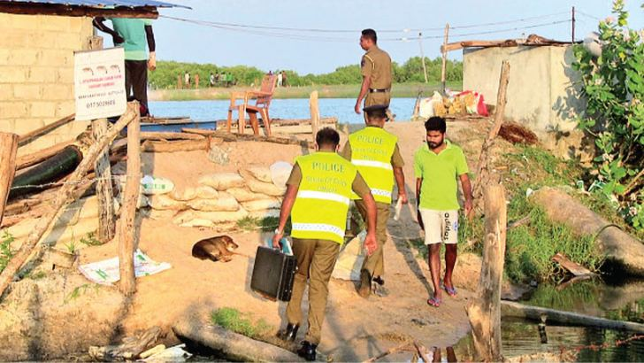 Police personnel inspecting the site where the body was found. Picture by Sivam Packiyanathan, Batticaloa Special Corr.