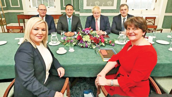Northern Ireland's new deputy First Minister Michelle O'Neill (Left) and First Minister Arlene Foster (Right) meet with members of the British and Irish governments in Belfast, Northern Ireland, after signing a deal to restore power-sharing on January 13, 2020.