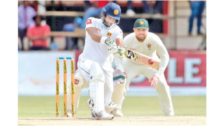 Sri Lanka's captain Dimuth Karunaratne (L) plays a shot as Zimbabwe's Brendan Taylor (R) looks on  during the second day of the second Test cricket match between Zimbabwe and Sri Lanka at the Harare Sports Club in Harare on January 28, 2020.