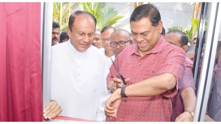 SLPP National Organiser Basil Rajapaksa checking his watch for the auspicious time before inaugurating the media centre, while Information and Communication Technology State Minister Lakshman Yapa Abeywardena and others look on.