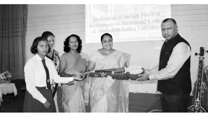 A group of school representatives receiving a musical instrument.