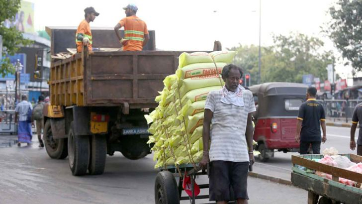 Goods being unloaded while sanitation workers also attend to their duties in the Pettah