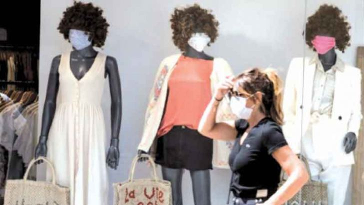 A woman wearing a face mask passes by a show window with masked mannequins in Mulhouse, eastern France. - AFP
