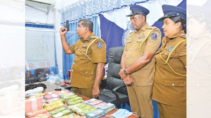 Police officers with the pistol used  and the robbed cash at the Maradana police station yesterday. Picture by Washitha Patabendige.