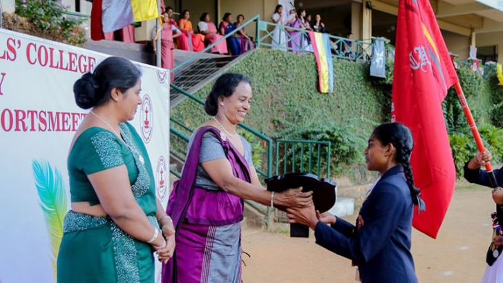 House Captain of the Champion Sangamitta House, Ravisha Bandara receiving the Champion Trophy from  the Chief Guest.