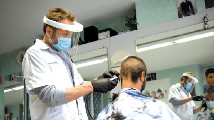 A hairdresser wearing a protective face mask and plastic gloves cuts the hair of a customer.