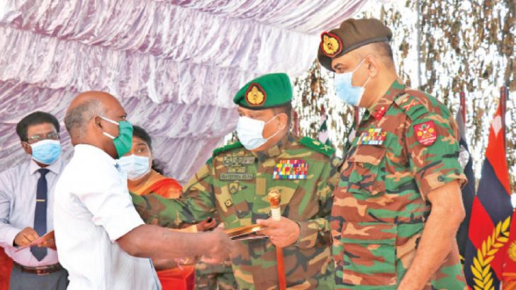 A recipient taking the deed from Army Commander Shavendra Silva.