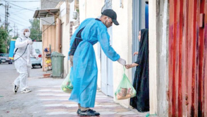 A volunteer provides food to a child in a residential neighbourhood of Karbala in Iraq after the imposition of curfews due to the coronavirus.