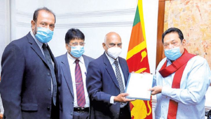 Committee members retired High Court Judge Gamini Sarath Edirisinghe, former Ministry  Secretary Gotabaya Jayaratne and senior lawyer Harigupta Rohanadheera handing over the report yesterday to Prime Minister Mahinda Rajapaksa. (Picture by PM's Media Unit).