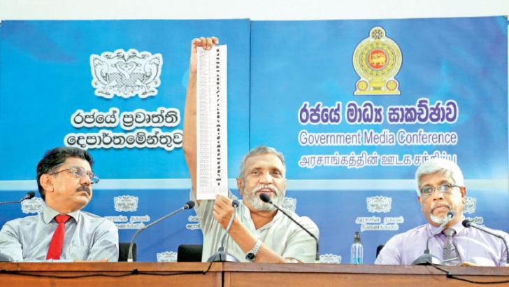 The Chairman of the Election Commission Mahinda Deshapriya, accompanied by health and security officials demonstrating health measures that will be in place at polling stations to prevent the spread of COVID-19 and other actions to ensure a free and fair poll on Wednesday. Pictures by Niroshan Batepola