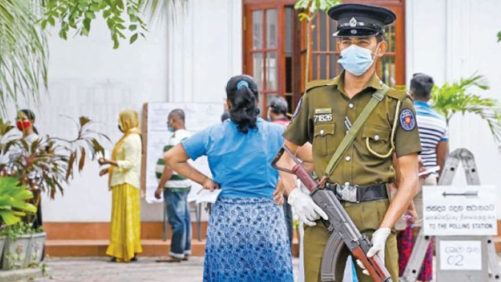 A policeman stands guard as voters wait in a queue to cast their ballots in the parliamentary election on Wednesday.