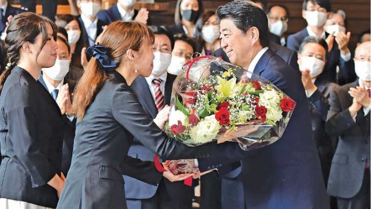 Japan's outgoing Prime Minister Shinzo Abe (C-R) receives flowers from the staff after his last Cabinet meeting at Prime Minister's office in Tokyo yesterday. - AFP