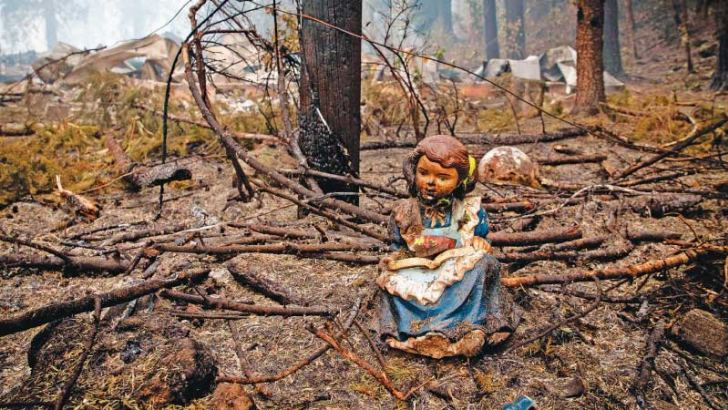 A statue of a girl reading sits in Blue River, Oregon near where the library stood before it was destroyed in the Holiday Farm Fire. - AFP