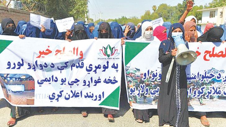 Afghan women hold banners and chant slogans in Jalalabad during a march to show their support for peace talks between Afghan government and the Taliban.