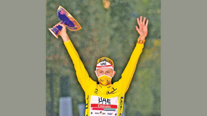 Team UAE Emirates rider Slovenia's Tadej Pogacar wearing the overall leader's yellow jersey celebrates on the podium after winning the 107th edition of the Tour de France cycling race. AFP