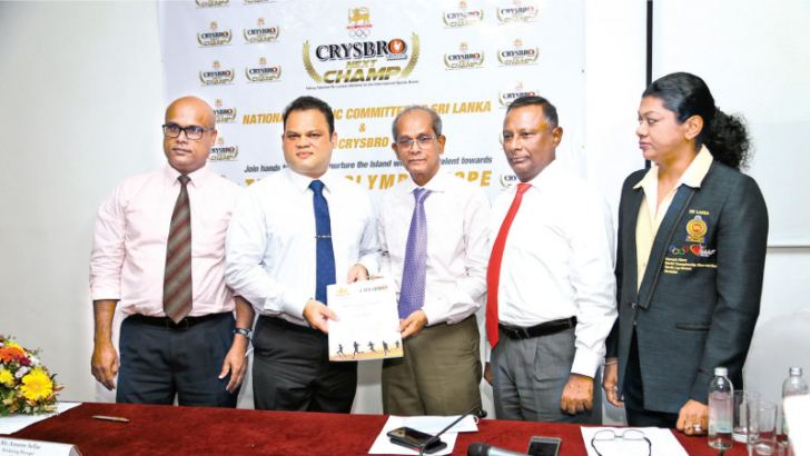 Amores Sellar, Senior Manager-Sales and Marketing, Crysbro (second from left) exchanging the agreement with Maxwell de Silva, Secretary General, NOC SL soon after signing the MOU. Others in the picture are from left-Nalin Aluthgamage, representative, Crysbro, Suresh Subramanaiam, President NOC SL, Susanthika Jayasinghe, Silver Medalist(200m) at 2000 Sydney Olympics Games. Picture by Sulochana Gamage