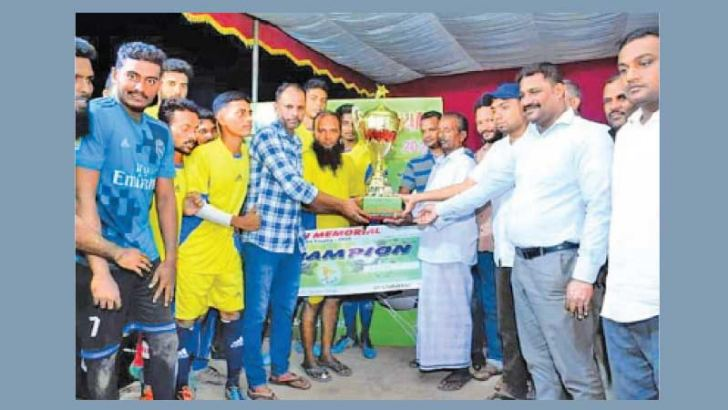 The skipper of the champions Akkaraipattu FSC team receiving the Musthafa Fahath Memorial Trophy from Akkaraipattu Municipal Councilor Azmi Abdul Gafoor