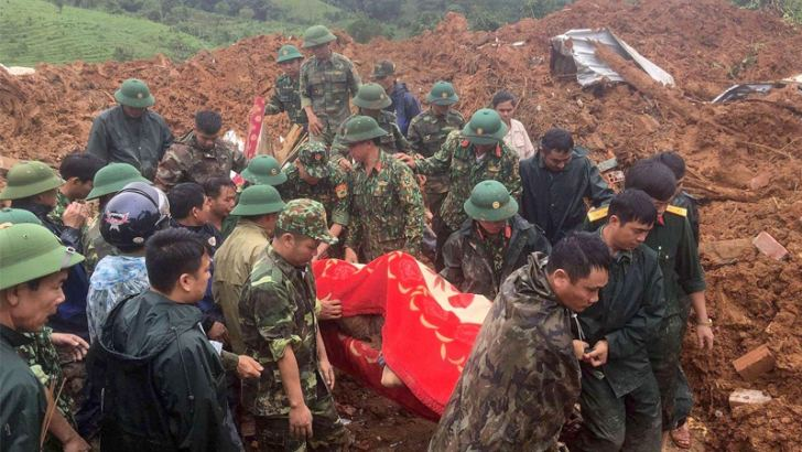 This picture taken on October 18, 2020 and released by the Vietnam News Agency on October 18, 2020 shows military personnel carrying a body recovered from the site of a landslide in central Vietnam's Quang Tri province.  AFP