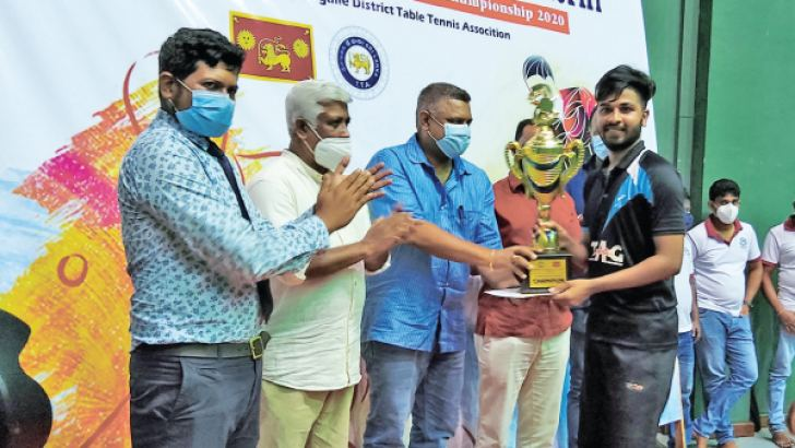 Krishan Wickremaratne receives the Maheepala Herath Challenge Trophy from the chief guest, State Minister Kanaka Herath