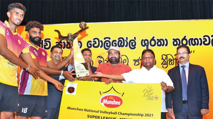 The Men's Champions of the 'Munchee National Super League Volleyball 2021, Ceylon Electricity Board skipper Deepthi Romesh Ranawake is seen receiving the Trophy from, Nalin P. Karunaratne and Deputy Speaker, President of SL Volleyball Federation Ranjith Siyambalapitiya and Minister of Power and Energy Dallas Alahapperuma.