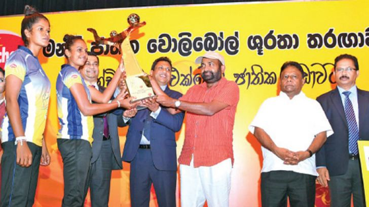 The victorious Sri Lanka Army Women's Volleyball team captain Thilini Wasana receiving 'Munchee National Super League Volleyball 2021 Award  from Chief Executive Officer Ceylon Biscuits, Nalin P. Karunaratne and Deputy Speaker and President of SL Volleyball Federation Ranjith Siyambalapitiya. Also in the picture is Minister for Power and Energy Dallas Alahapperuma.