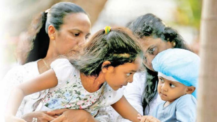 A child consoles another who is a victim of the blasts. Pictures by Sulochana Gamage
