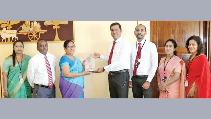 People's Bank CEO/GM Ranjith Kodituwakku handing over a plaque to commemorate the historical transaction of CEB to GM (Eng) Kumudini Herath