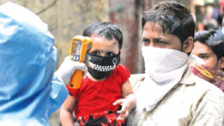 A health worker checks the temperature of a child in India's                                                                  Maharashtra State.
