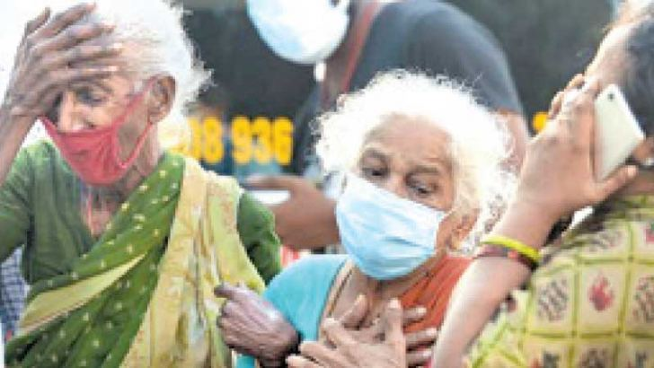 Relatives outside a mortuary in Chennai on Wednesday mourn the death of their loved one who died due to COVID-19. - ASSOCIATED PRESS