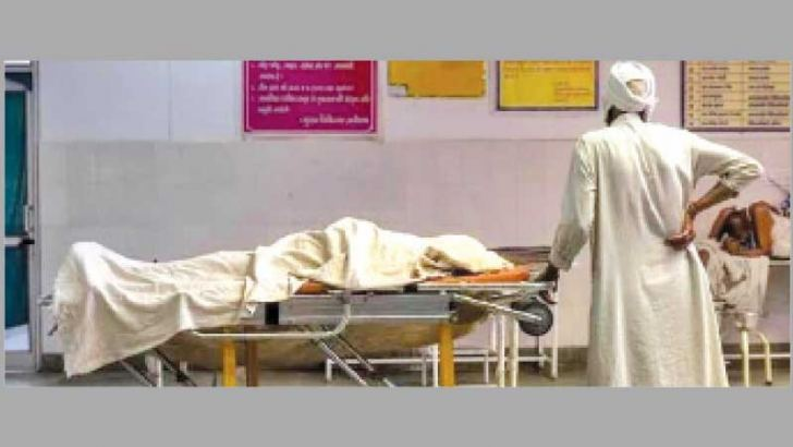 A man stands next to the body of his wife who died due to breathing difficulties from COVID-19 in Bijnor, Uttar Pradesh, India on Tuesday. - PTI