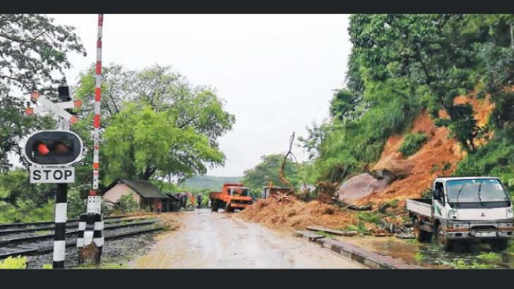 Railway Department and Road Development Authority officials clearing the debris from the road.
