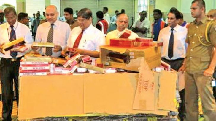 Customs officials with the cigarettes. Picture by Kumarasiri Prasad
