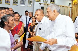 The Government decided to write-off micro-finance loans of Rs.100,000 or less obtained by women in regions affected by drought especially in the Northern and North-Central Provinces. Here, Prime Minister Ranil Wickremesinghe handing over the relevant documents to beneficiaries during an event at the Jaffna District Secretariat yesterday. Finance and Mass Media Minister Mangala Samaraweera was also present. Picture by Rukmal Gamage