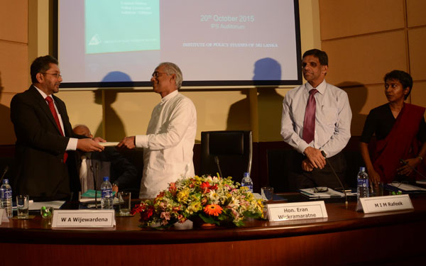 IPS Executive Director, Dr. Saman Kelegama hands over a copy of the State of the Economy Report 2015 to Hon. Deputy Minister of State Enterprise Development, Eran Wickramaratne. Former Deputy Governor, Central Bank of Sri Lanka, W AWijewardena,the Secretary to the Ministry of National Planning and Economic Affairs, M I M Rafeek, and IPS Deputy Director, Dr. Dushni Weerakoon looks on.