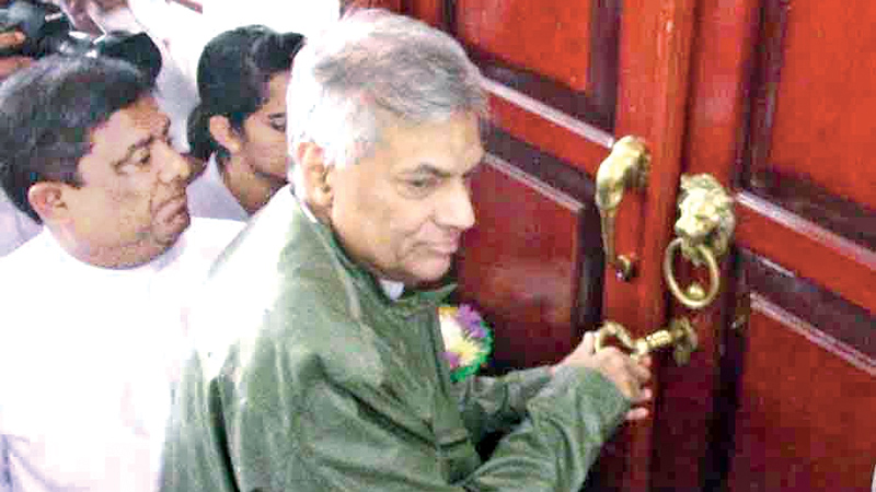 Prime Minister Ranil Wickremesinghe unlocks the entrance door of the newly built Buddha Mandira to mark the inauguration. Minister Vajira Abeywardana is also in the picture. Picture by Mahinda P.Liyanage- Galle Central Special Correspondent