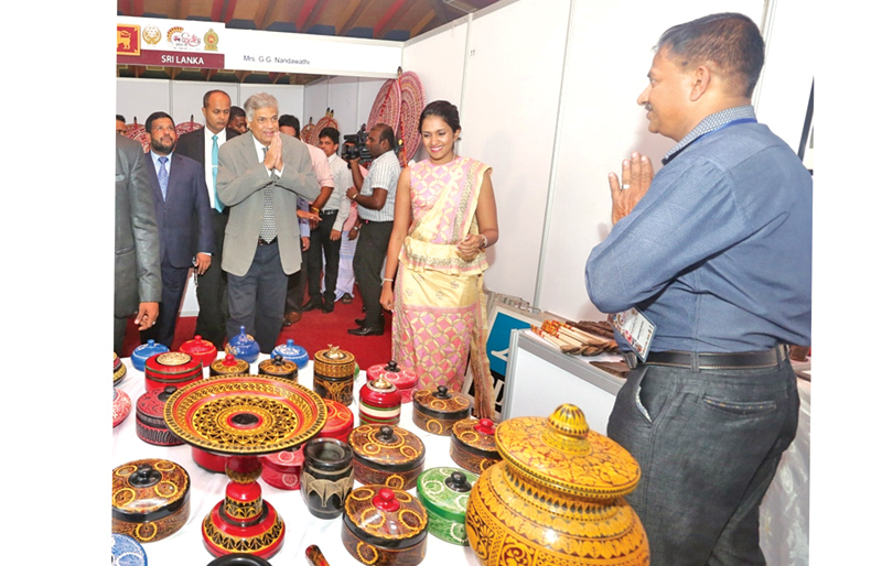 Prime Minister Ranil Wickremesinghe at a stall at the Shilpa Abhimani and SAARC handicraft exhibition organised by the SAARC Cultural Centre National Handicraft Council at the BMICH yesterday.