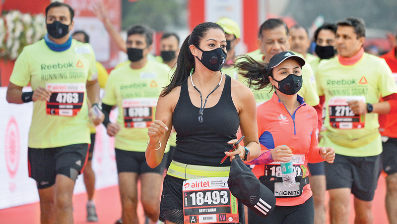Men and women wear face masks as they take part in the Delhi half marathon in New Delhi on Sunday. AFP