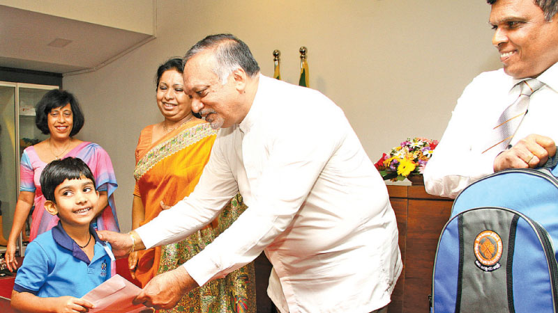 Labour and Trade Union Relations Minister Ravindra Samaraweera granting a scholarship to a dependent of an employee who had either passed away or suffered from a full or partial disability while on official duties. (Picture by Sulochana Gamage)