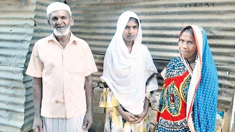 Musadika Fathima and her parents outside their home in Fazi Nagar, Muttur.