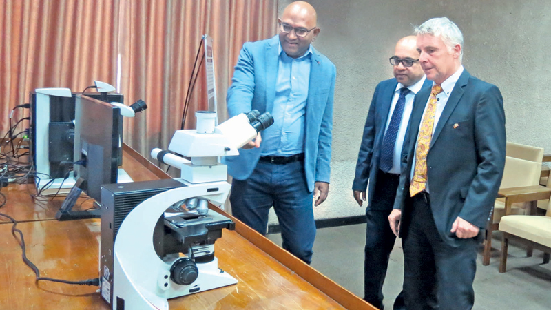 Researchers inspecting  the Leica DM3000 research microscope at the National Institute of Fundamental Studies, a Ecology Evolution and Biodiversity project in Kandy.